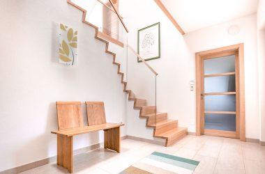 Großzügiges Treppenhaus mit eleganter Wendeltreppe aus Massivholz und Glasgeländer (Foto: Akkurat Identity)